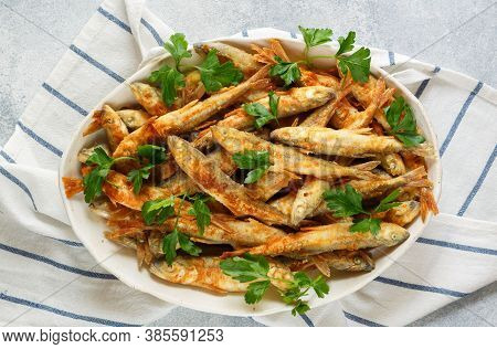 Fried Smelt. Delicious Small Fish With Fresh Parsley In A White Plate. Gourmet Appetizer. Selective