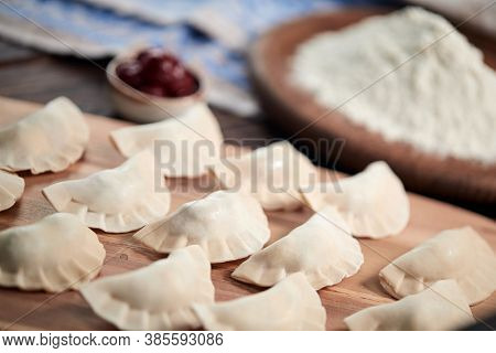 raw dumpling with cherries on the wooden board
