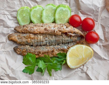 Fried Capelin With Cucumbers, Cherry Tomatos, Lemon And Parsley On The Paper. Top View