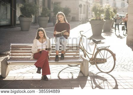 two young girls read a book on a bench