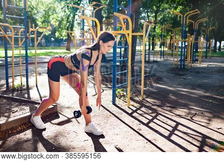 Fit Brunette Gorgeous Woman Training Using Dumbbell In Park, Sports Ground. Young Female With Elasti
