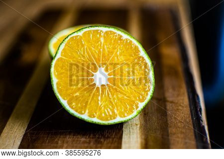 Bergamot Slices On Wooden Background Lined Up In A Stacked Order.