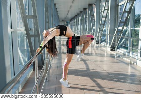 Side View Of Muscular Brunette Woman Practicing Gemnastics Pose. Young Flexible Female Athlete Posin