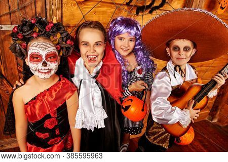 Joyful funny kids in carnival costumes celebrate halloween together. Wooden decorations with pumpkins, spider web and spider. Halloween. Dia de los muertos. Day of The Dead.