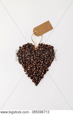 Coffee beans in shape of heart on white background, flat lay