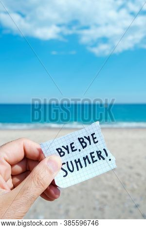 closeup of the hand of a young caucasian man on the beach, in front of the ocean, holding a piece of paper with the text bye bye summer written in it