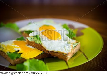 Fried Toast With Cheese Spread Of Arugula And Fried Egg In A Plate