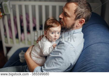 Middle Age Caucasian Father Hugging Newborn Baby. Male Man Parent Holding Child On His Arms. Authent