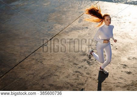 Image of redhead focused girl running while working out on promenade at sunrise