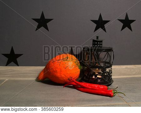 Pumpkin, Red Pepers And Jack O'lantern Against A Black Wall With Stars. Lantern With Candles