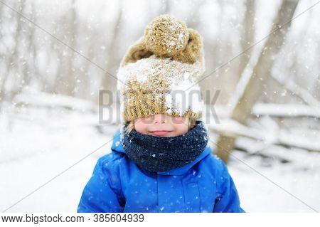 Funny Little Boy In Blue Winter Clothes Walks During A Snowfall. Outdoors Winter Activities For Kids