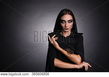 Mysterious Witch With Spooky Spider On Dark Background. Space For Text