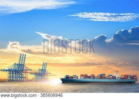 Container Cargo Ship With Working Crane Bridge In The Seaport At Sunset Sky, Global Business Logisti
