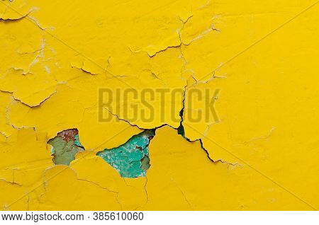 Texture concrete industrial background - light yellow and green peeling paint on the old rough concrete surface, peeling paint texture. Texture background with peeling paint
