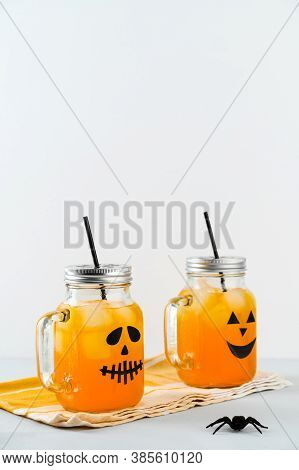 Iced Pumpkin Cocktails In Glass Jars Decorated With Scary Faces On The Gray Table, White Background.