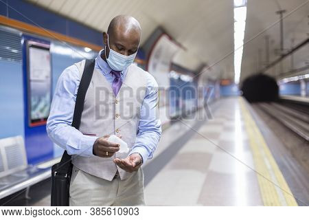Black Man With Face Mask Putting Sanitizing Gel On His Hands. He Is Inside A Subway Station. Concept