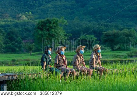 Group Of America Boy Scouts Wearing Protective Mask To Protect Against Covid-19 Sitting In Green Fie