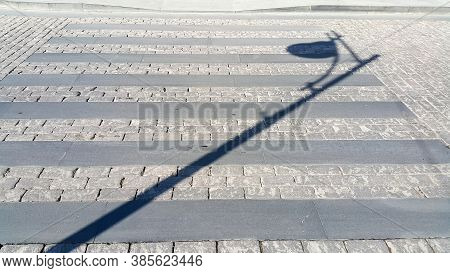 Pedestrian Crosswalk Made Of Stones. Shadow Of A Pole Lighting The Street. Paved Path. Cross The Roa