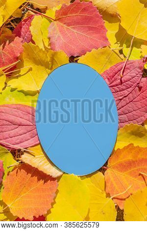 The Mirror Lies On Autumn Yellow And Red Leaves. The Cloudless Blue Sky Is Reflected In The Mirror.