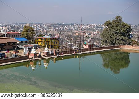 Bhaktapur, Kathmandu, Nepal - December 23, 2019: View Over A Pond With Unidentified People And The N