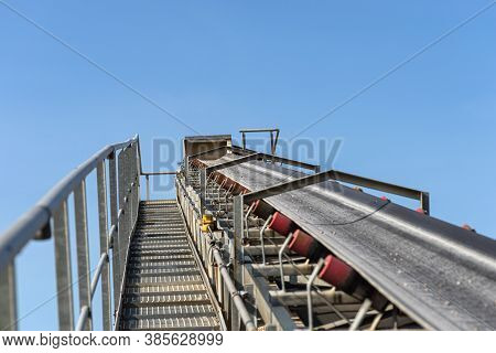 Close-up Shot Of The Conveyor Belt In The Concrete Plant With Transport Rollers, Visible Metal Stair