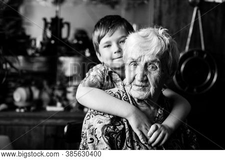 An old woman with her little grandson, closeup portrait. Black and white photography.