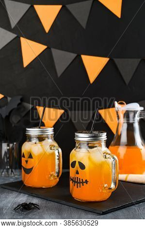 Iced Pumpkin Cocktails In Glass Jars Decorated With Scary Faces On A Dark Table. Diy Halloween Party