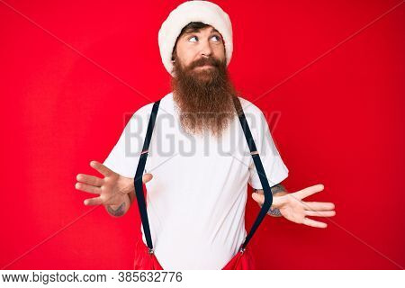 Handsome young red head man with long beard wearing santa claus costume with suspenders smiling looking to the side and staring away thinking.