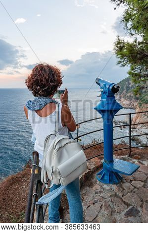 Woman Taking A Photo Of The Coastal Landscape With Her Smartphone, From A Viewpoint