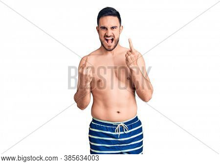 Young handsome man wearing swimwear showing middle finger doing fuck you bad expression, provocation and rude attitude. screaming excited
