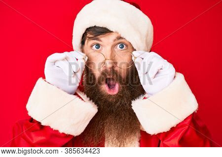 Handsome young red head man with long beard wearing santa claus costume and glasses in shock face, looking skeptical and sarcastic, surprised with open mouth