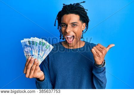 Young african american man holding south african 100 rand banknotes pointing thumb up to the side smiling happy with open mouth