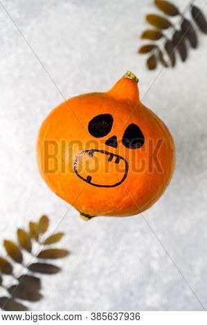 Top View Halloween Pumpkin With Painted Face And Autumn Decorations On A Shiny Silver Background. Ve