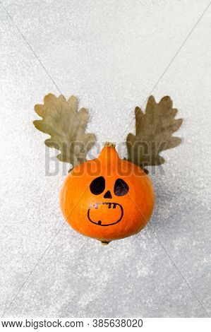 Top View Halloween Pumpkin With Painted Face And Horns Made From Autumn Leaves On A Shiny Silver Bac
