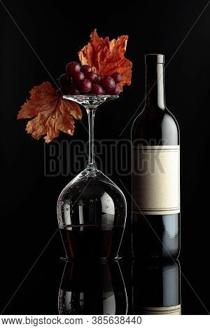 Bottle Of Red Wine And An Inverted Wine Glass With Wine On A Black Background. Wine With Grapes And