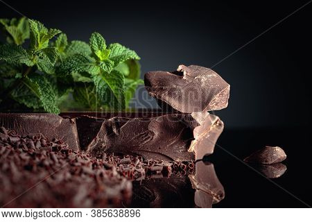 Pieces Of Dark Bitter Chocolate And Chocolate Chips With Mint On A Black Reflective Background. Copy