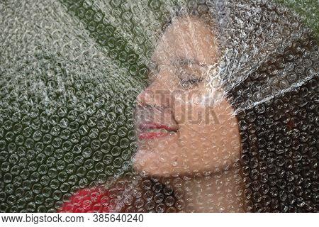 Soft Blurry Photo Through Polyethylene. Model Girl Posing Through Polyethylene Film. Portrait Of Bea