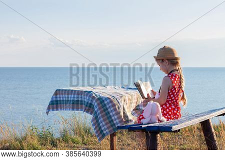 Child Girl In A Straw Hat And Dress Sitting On Bench And Reading Book. Cute Kid With Soft Rabbit Toy