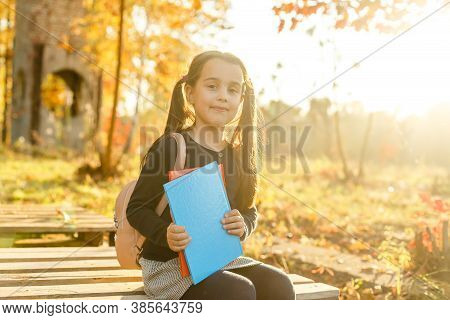 Keep Studying. Little Child Enjoy Learning In Autumn Park. Kid Study With Book. Small Girl Read Book