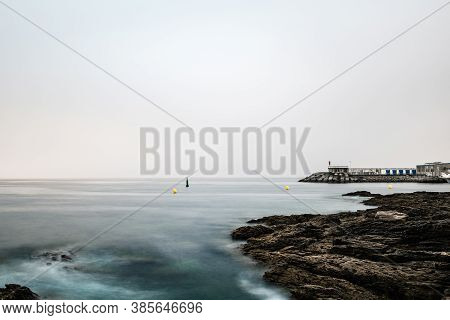 Rocks And Small Lighthouse On A Calm Foggy Evening In The Rias Baixas In Galicia, Spain. Long Exposu
