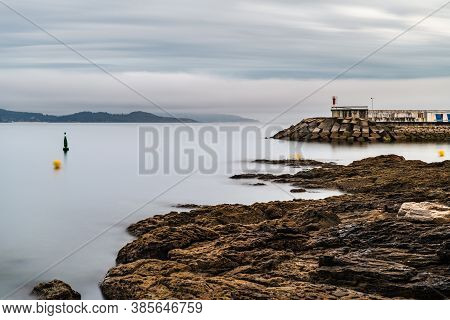 Rocks And Small Lighthouse On A Stormy Evening In The Rias Baixas In Galicia, Spain. Long Exposure.