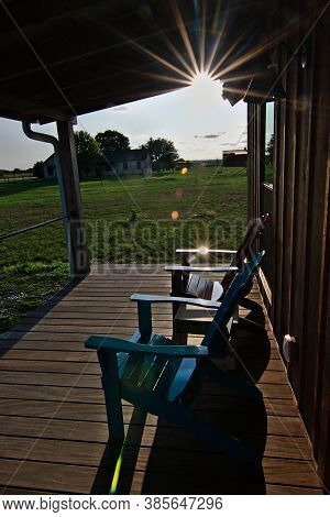 Adirondack Chairs Sitting On Sunny Porch Of Cabin Rental In Wine Country Texas With Sun Star And Fla