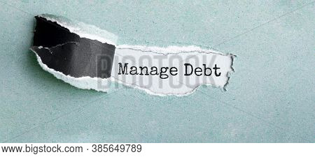 The Text Manage Debt Appearing Behind Torn Brown Paper