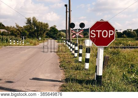 Railroad Crossing With A Stop Sign. Train Rails In Country Landscape. Railroad Tracks At Sunset Time