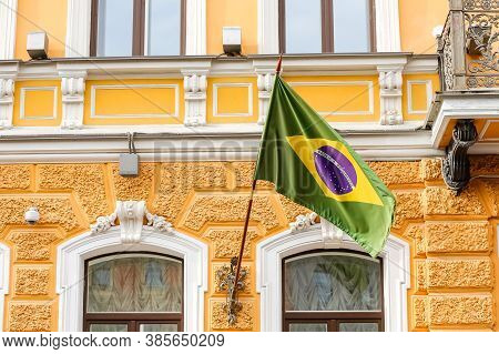 The Green Flag Of The Country Of Brazil Flutters In The Wind Against The Yellow Wall Of The House.fa