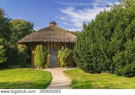 Beautiful Pavilion Or Garden House In Public Garden Park. Nice Summer Day With Blooing Trees And Gre