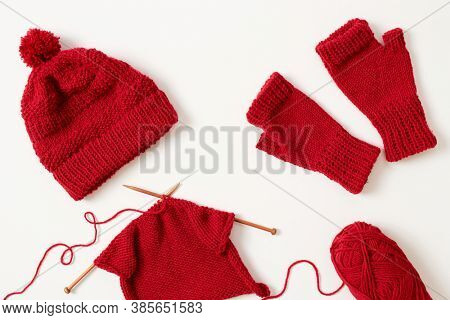 Knitting project in progress. Winter hat and mittens knitted with red yarn on white background.