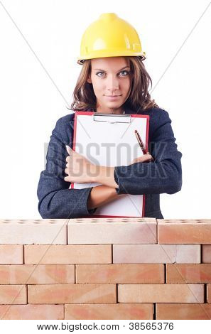 Woman builder and brick wall