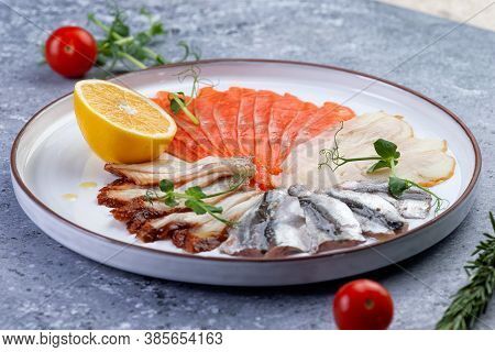 Fish Platter And Lemon In A Plate. On A Gray Background.