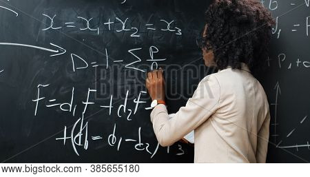 Back View On African American Young Woman Teacher At School Writing Formulas And Mathematics Laws On